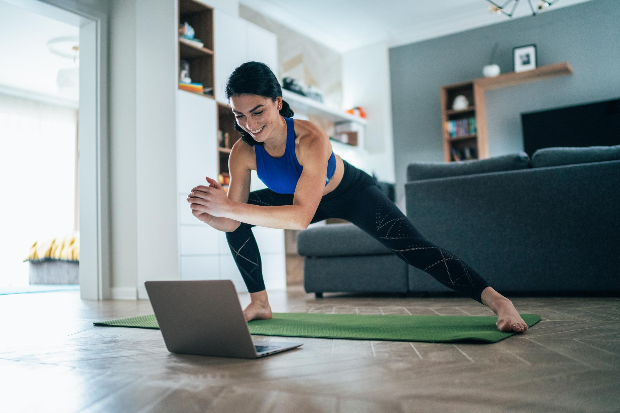 Woman stretching at home with laptop